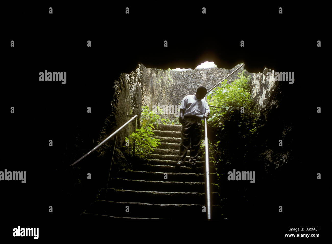 Young man at the entrance to the cave or slave chamber used to house slaves at Mangapwani Zanzibar Tanzania East Africa - Stock Image
