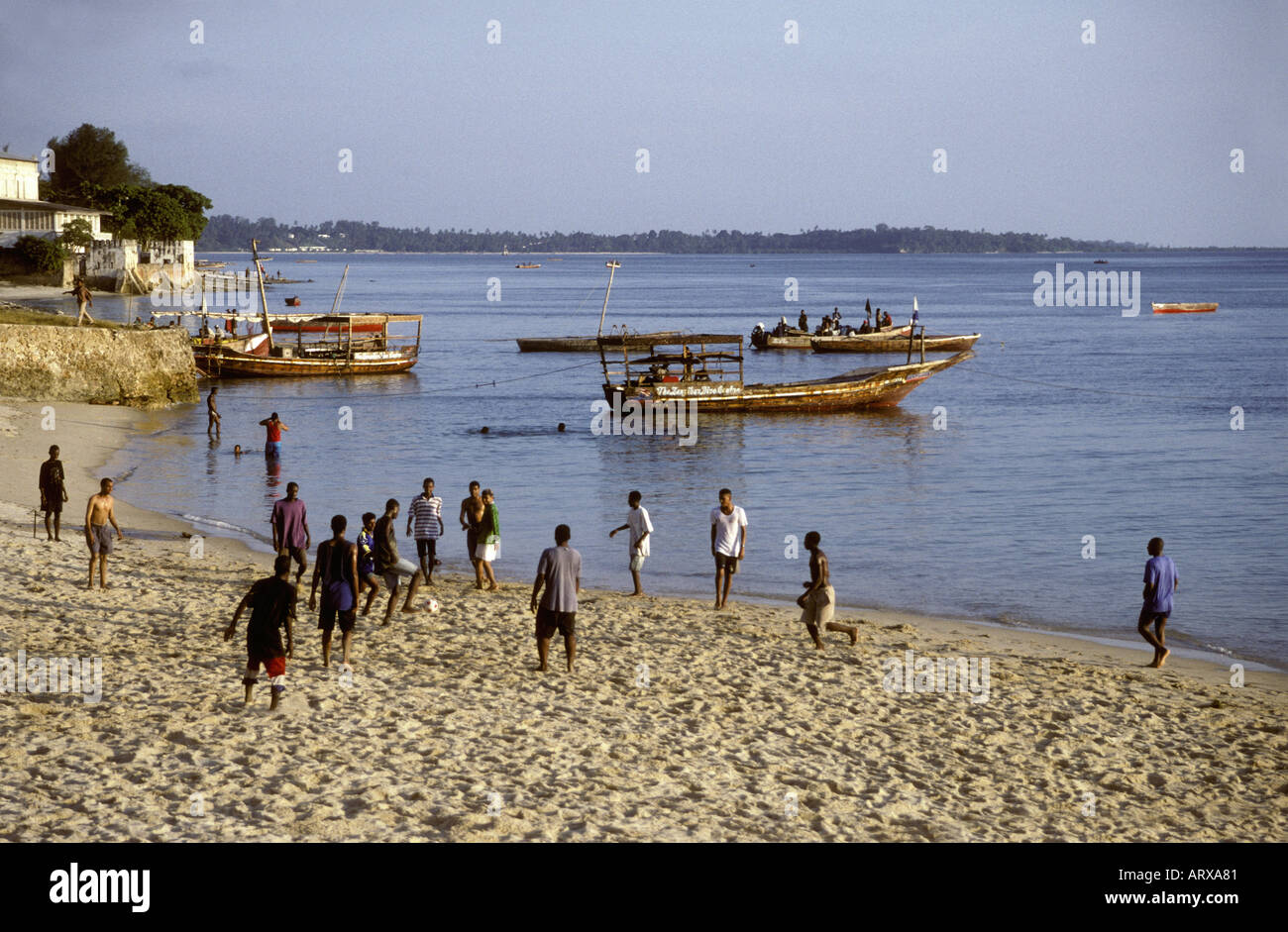 A group of young men playing soccer or football on a sandy beach near the stone town Zanzibar Tanzania East Africa - Stock Image