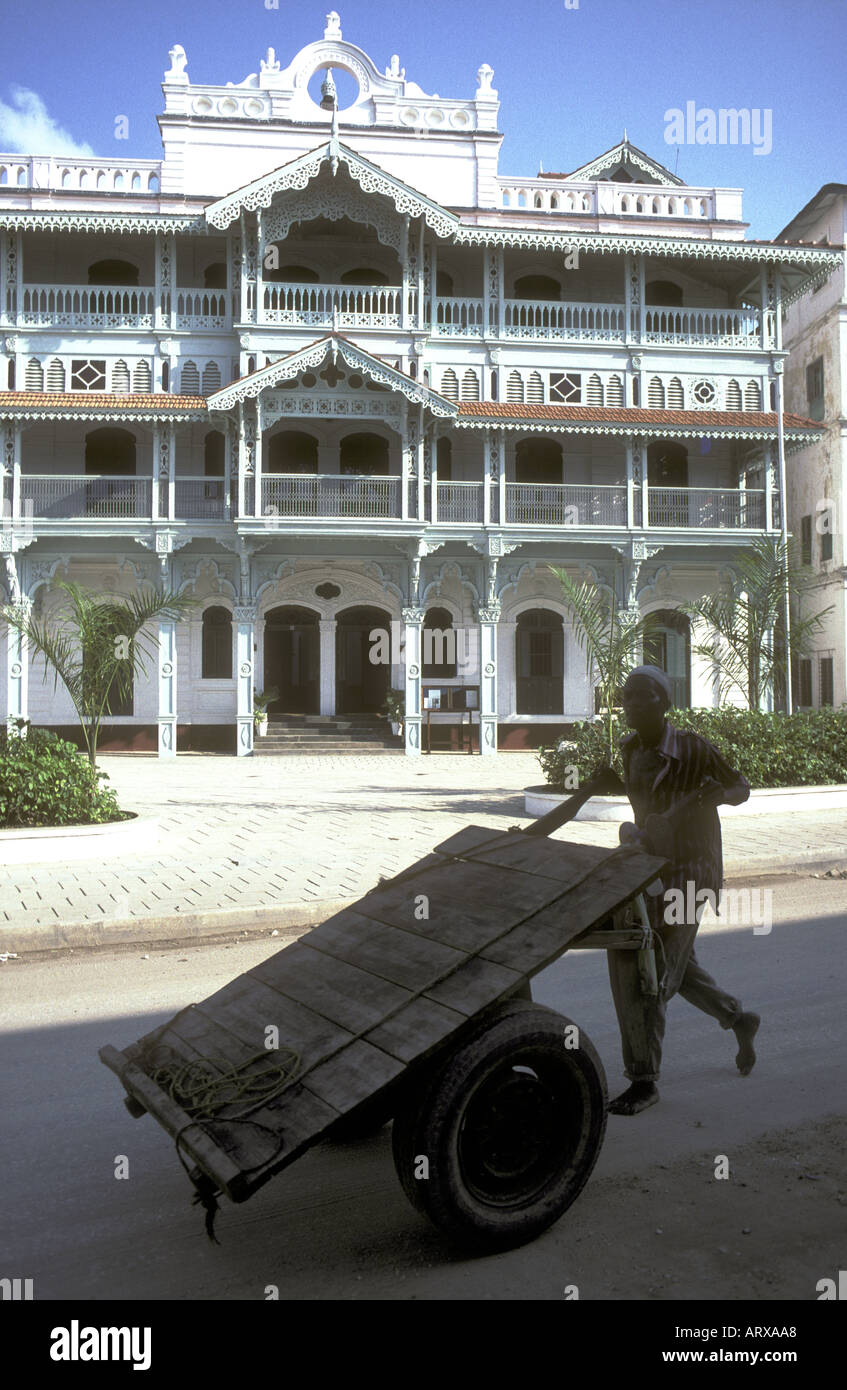 Man pushing cart or barrow past the Old Dispensary Zanzibar Tanzania East Africa - Stock Image