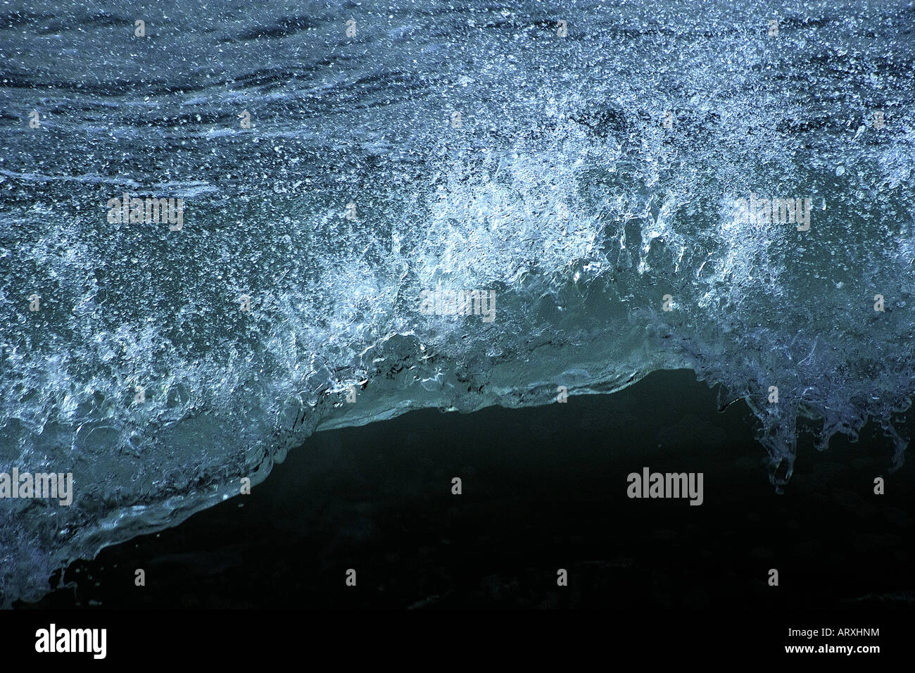 Darkened photograph of a breaking wave. Fast shutter speed stops the action. - Stock Image