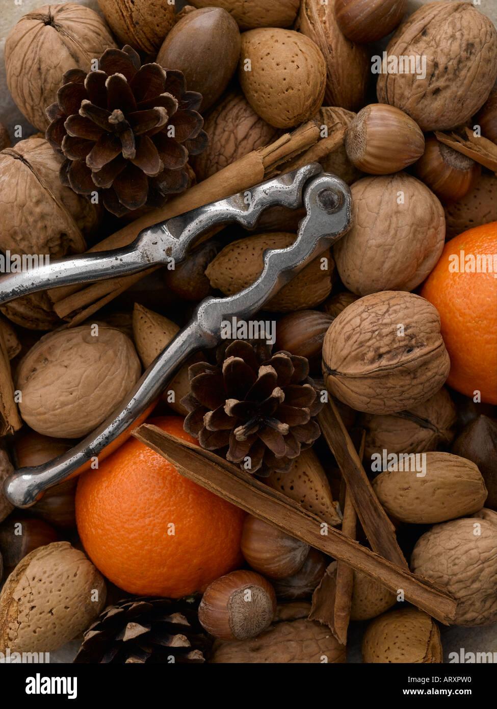 Mixed nuts satsumas cinnamon sticks and nut crackers - Stock Image