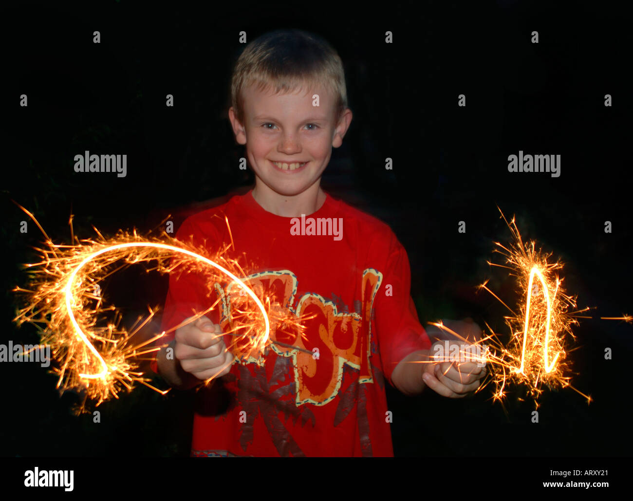 Boy Using A Firework Sparklers To Paint With Light. - Stock Image