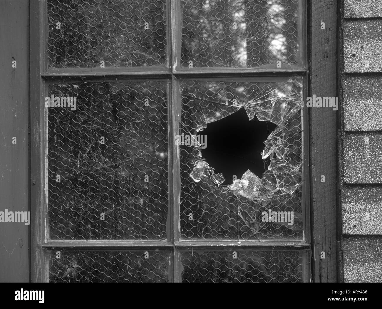 A broken window in an abandoned shack - Stock Image