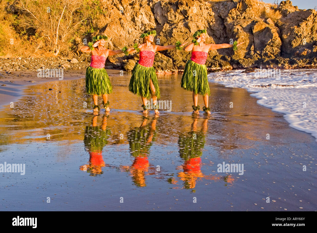 Three hula dancers in ti leaf skirts dance at the water's edge with their reflection at Olowalu, Maui. Stock Photo