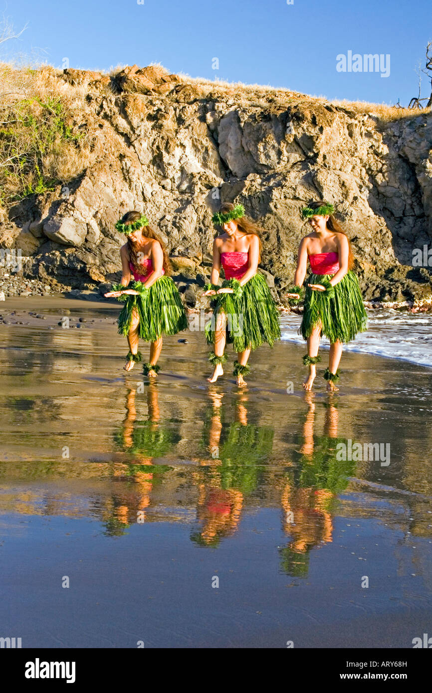 Three hula dancers in ti leaf skirts dance at the water's edge with their reflection at Olowalu, Maui. - Stock Image