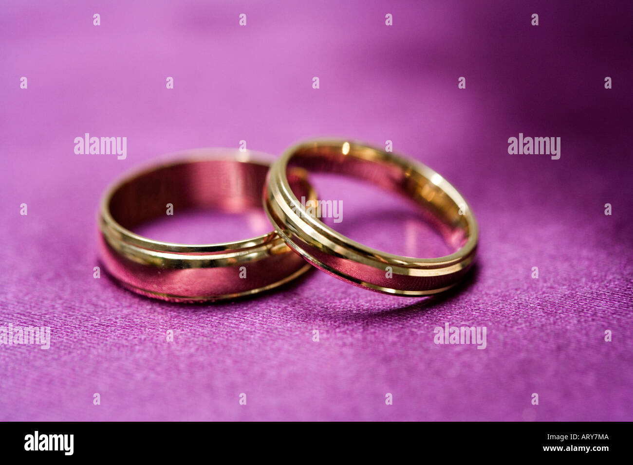 His and Her Wedding rings resting on purple cloth Stock Photo ...