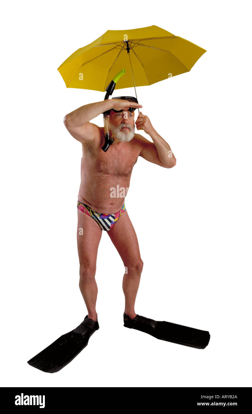 Humerous image of an active senior male in bikini brief wearing diving fins and holding an unbrella - Stock Image