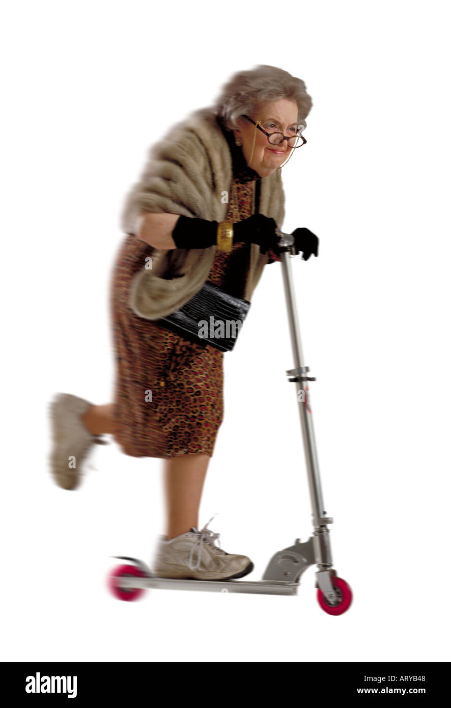 Humerous image of an elderly woman dressed up wearing a fur wrap and riding a scooter - Stock Image