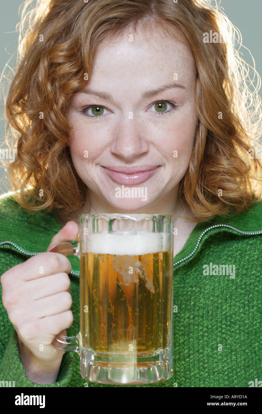 Redheaded woman with mug of beer - Stock Image
