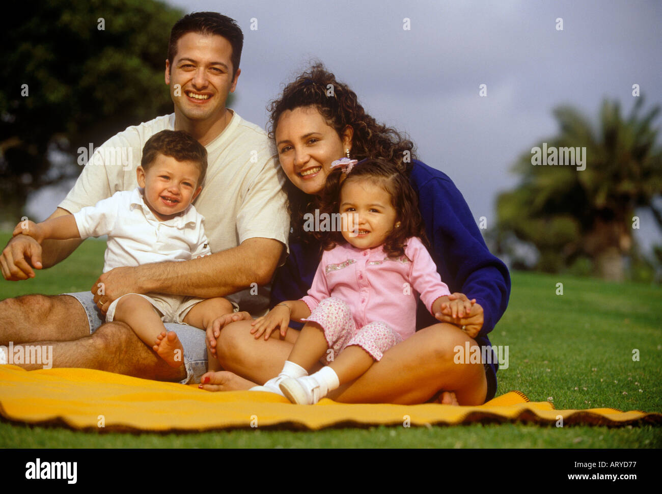 Young hispanic family sitting on a blanket in a park - Stock Image