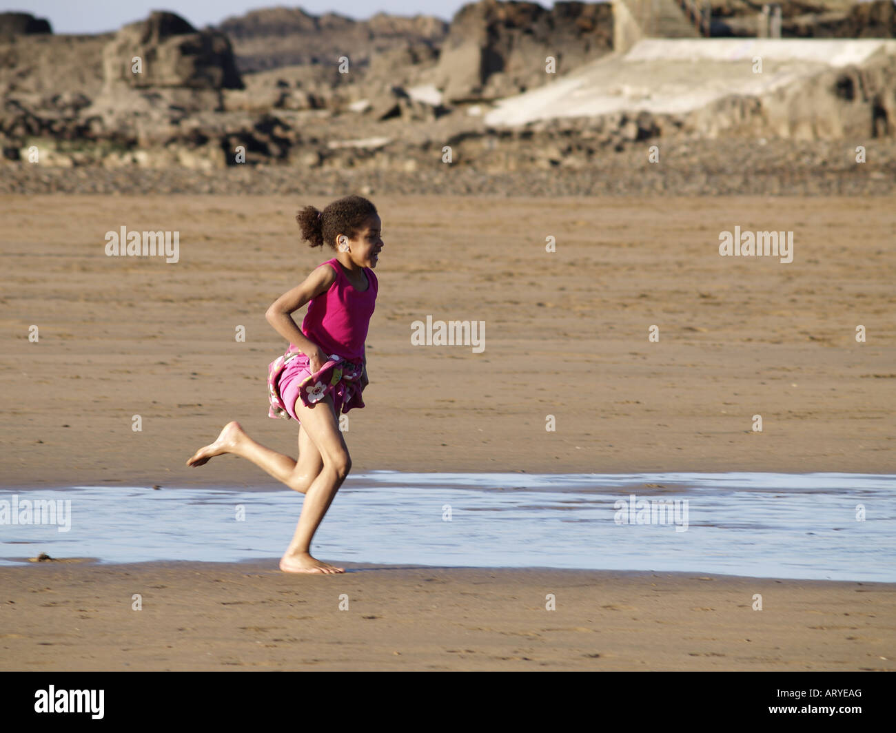 Young coloured girl running on a sandy beach in Cornwall - Stock Image