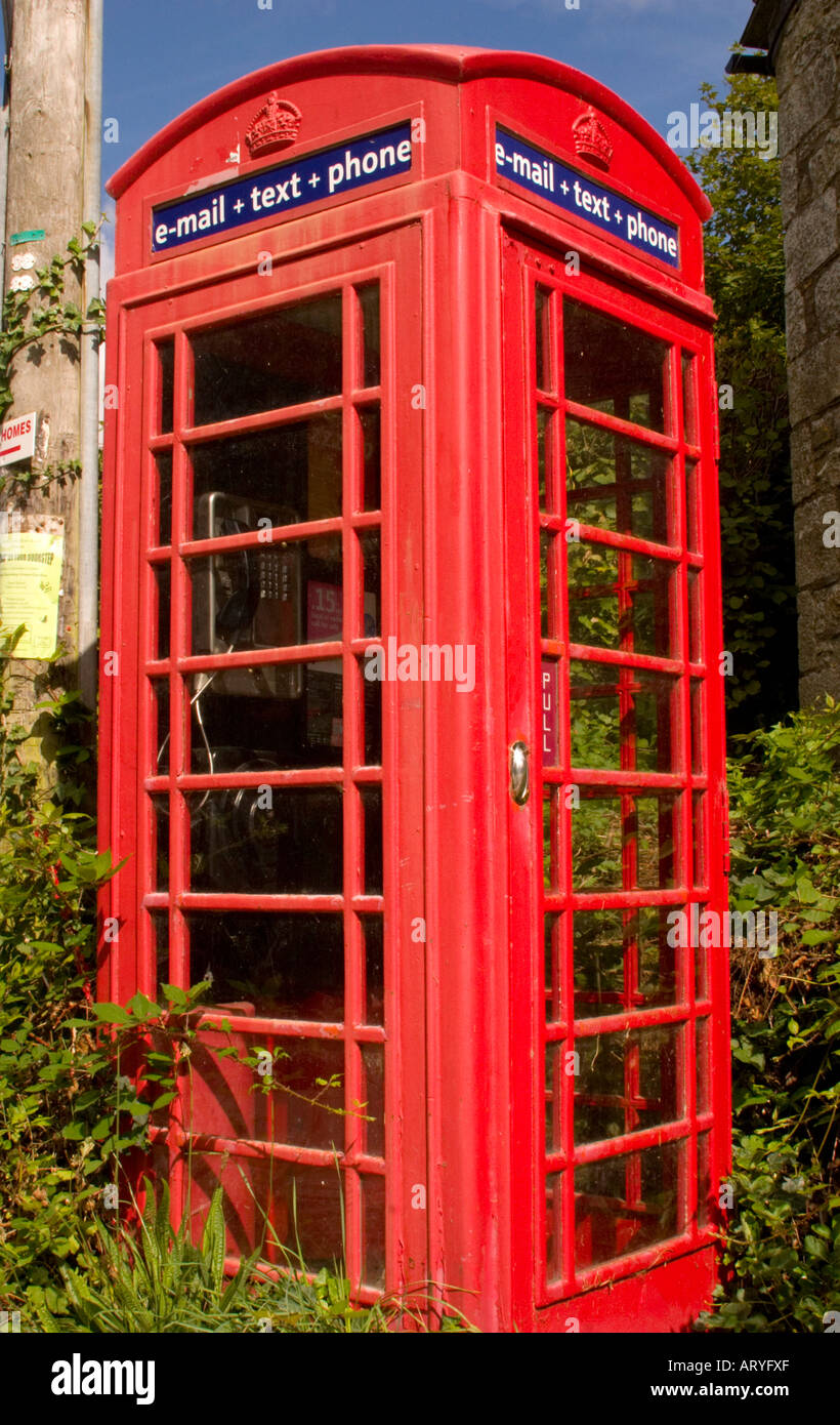 Traditional red telephone box offering email and texting facilities for the local community in a rural village in Cornwall, UK - Stock Image