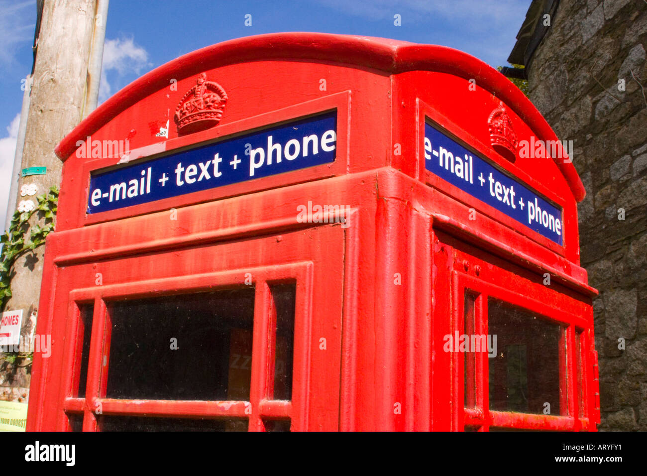 Traditional red telephone box offering email and texting services for the local community in rural  village - Stock Image