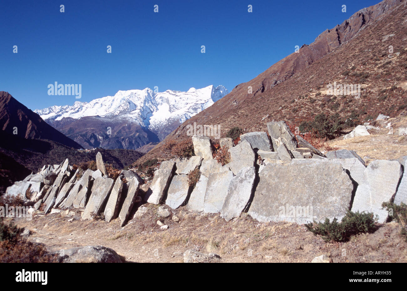 Manni stone with Kwande (6187m) above, Tengboche in the mid-distance. - Stock Image