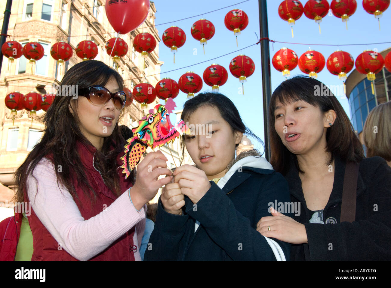 Three women on the streets of London in Chinatown to celebrate the Chinese New Year 2008 - Year of the rat - Stock Image