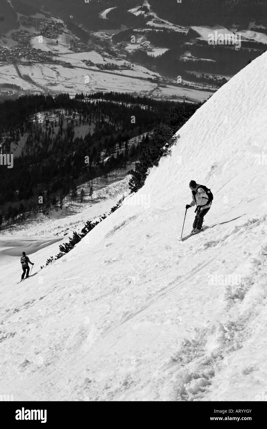 Wilderness skiers skiing into the valley - Stock Image
