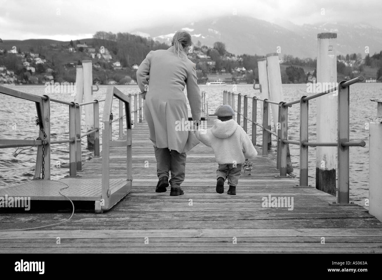 Life s a journey mother and toddler walk on a peer by lake lucerne - Stock Image