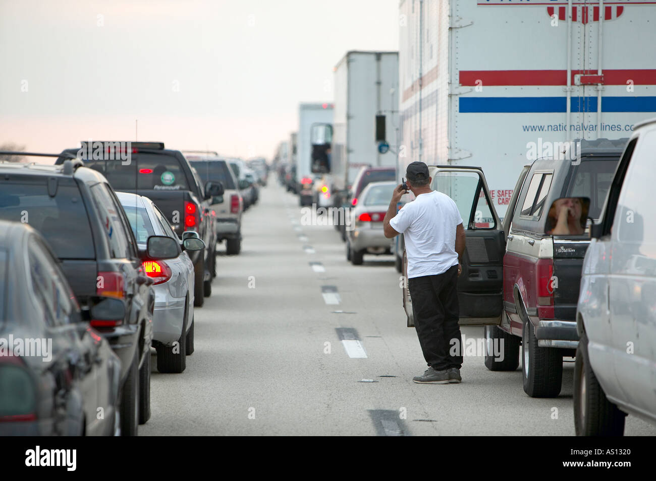 Man on cell phone looks down row of cars and trucks stopped in a traffic jam on Alligator Alley Florida Everglades - Stock Photo