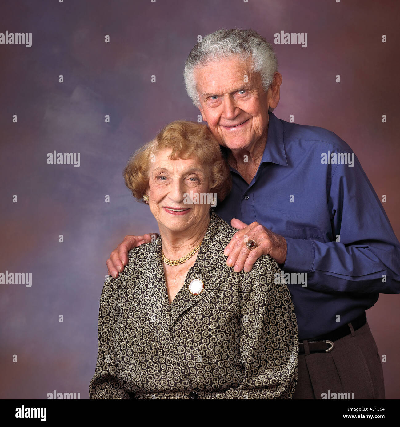 An senior couple portrait man standing behind woman his hands on her shoulders against a modeled background - Stock Image