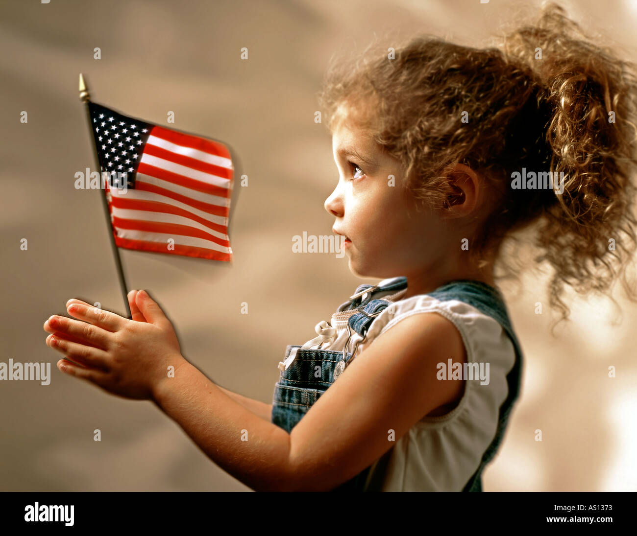 cfcd0f44c5df5 Young girl with brown hair in ponytail holding American flag in both ...