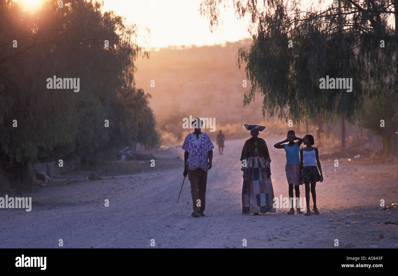 Herero family strolling down a dusty street at dusk Opuwo Namibia - Stock Image