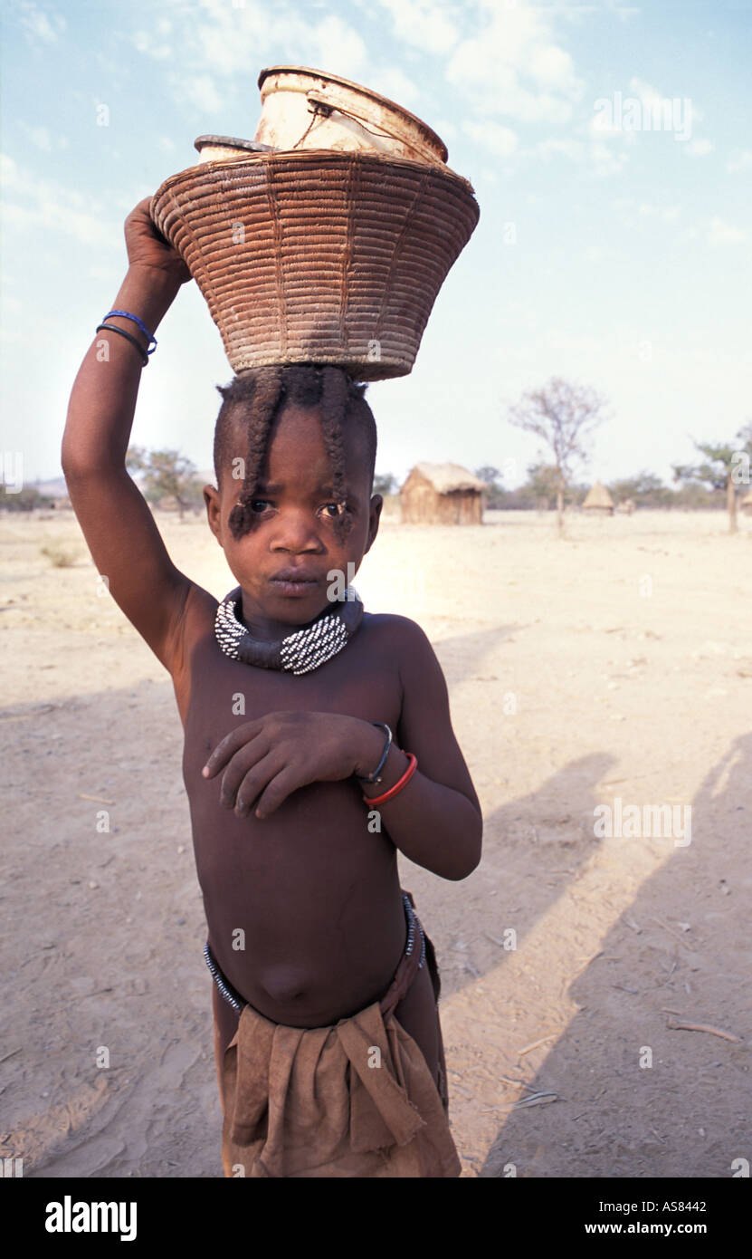 Himba girl photographed in her village carrying container on head Kaokoveld tribal areas North west of Opuwo Namibia - Stock Image