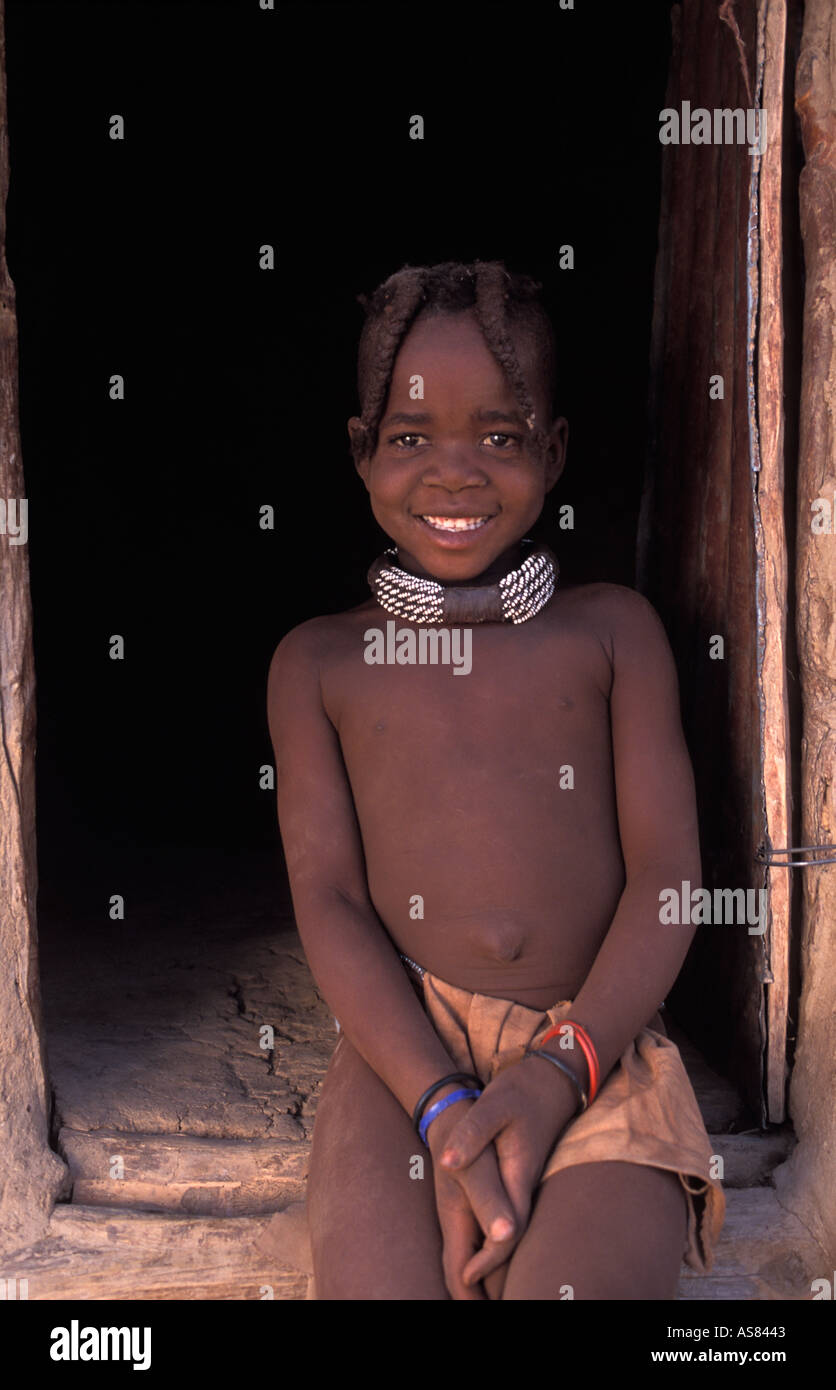 Himba girl photographed at the entrance to the granary hut Kaokoveld tribal areas North west of Opuwo Namibia Stock Photo