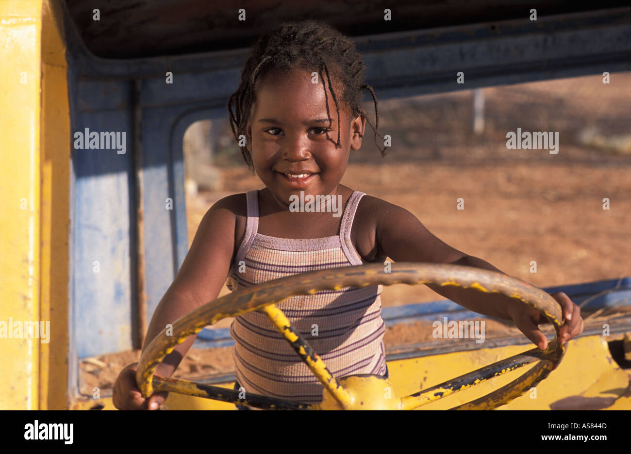 Young happy local girl in the brightly painted cab of an old broken down truck Opuwo Namibia - Stock Image