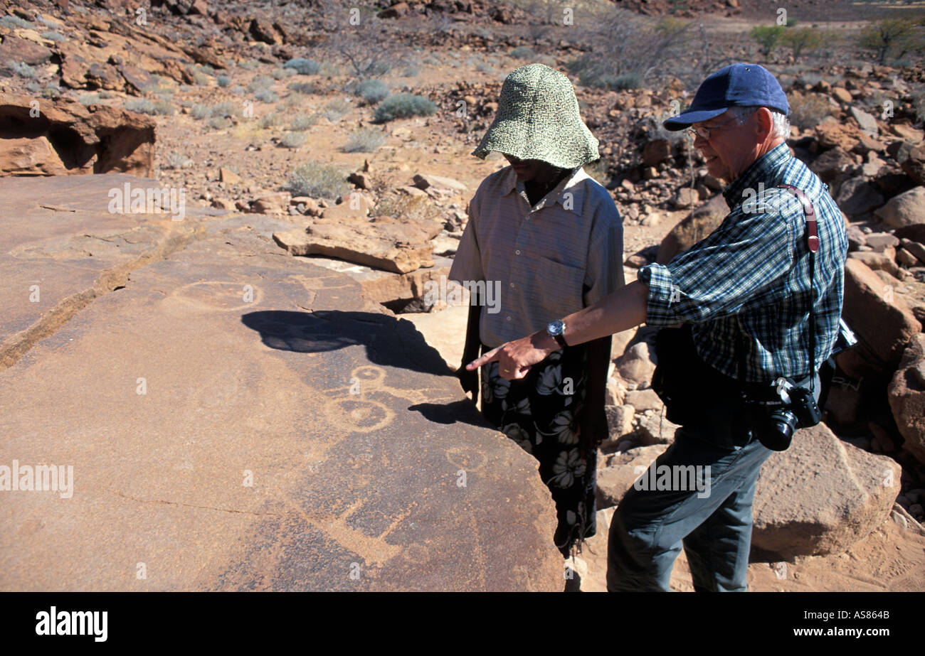 Local girls act as guides to show visitors the ancient petroglyphs at Twyfelfontein Namibia - Stock Image