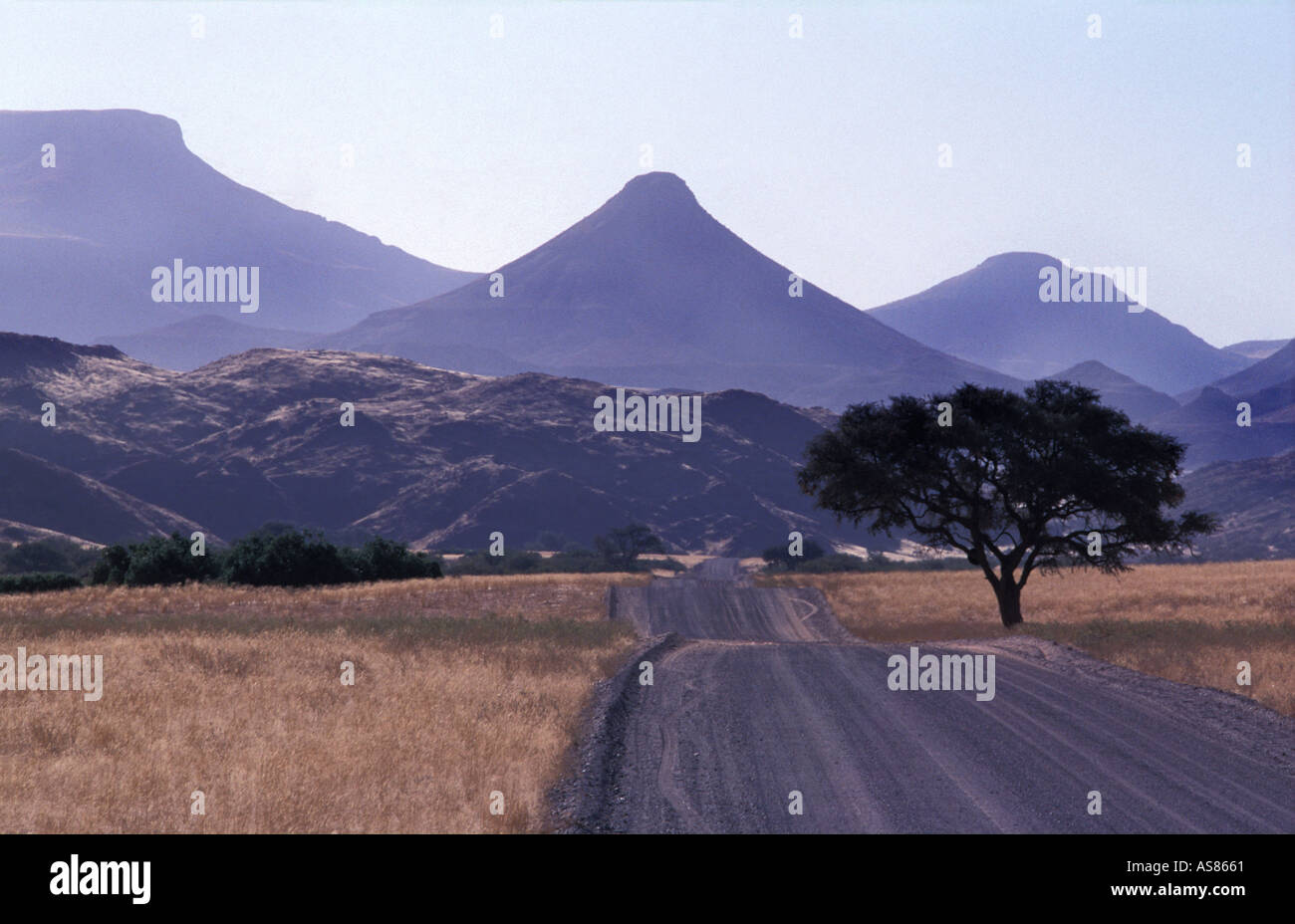 A prehistoric landscape gravel roads Palmwag to Sesfontein Extinct volcanoes tabletop mountains line the horizon Namibia - Stock Image