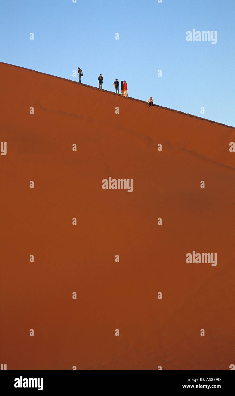 Early morning sun lights Dune 45 travellers climb to the summit Namib Naukluft National Park Namibia - Stock Image