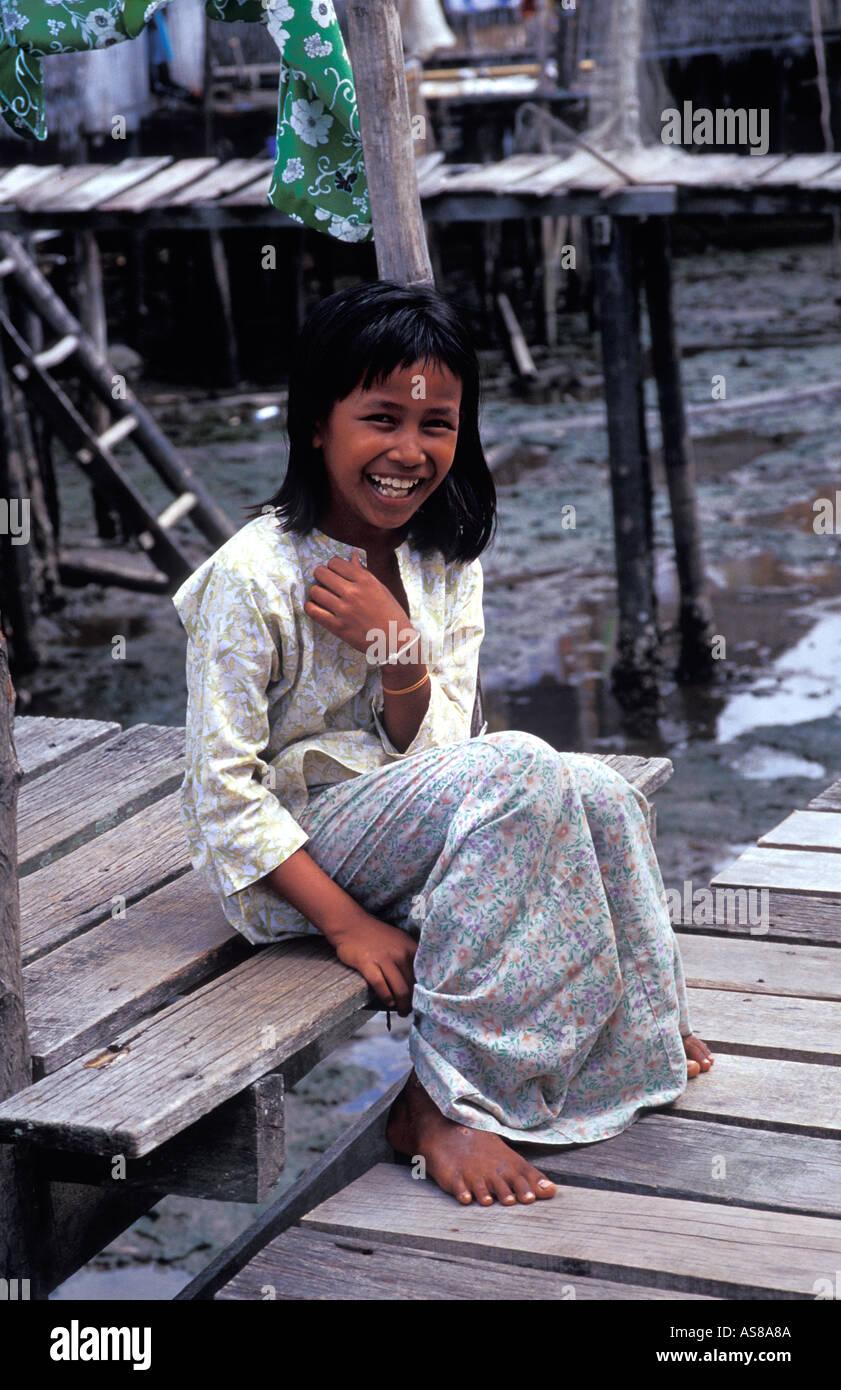 Malaysian girl from a local coastal community seated on a boardwalk nr Kota Kinabalu Sabah Malaysia - Stock Image