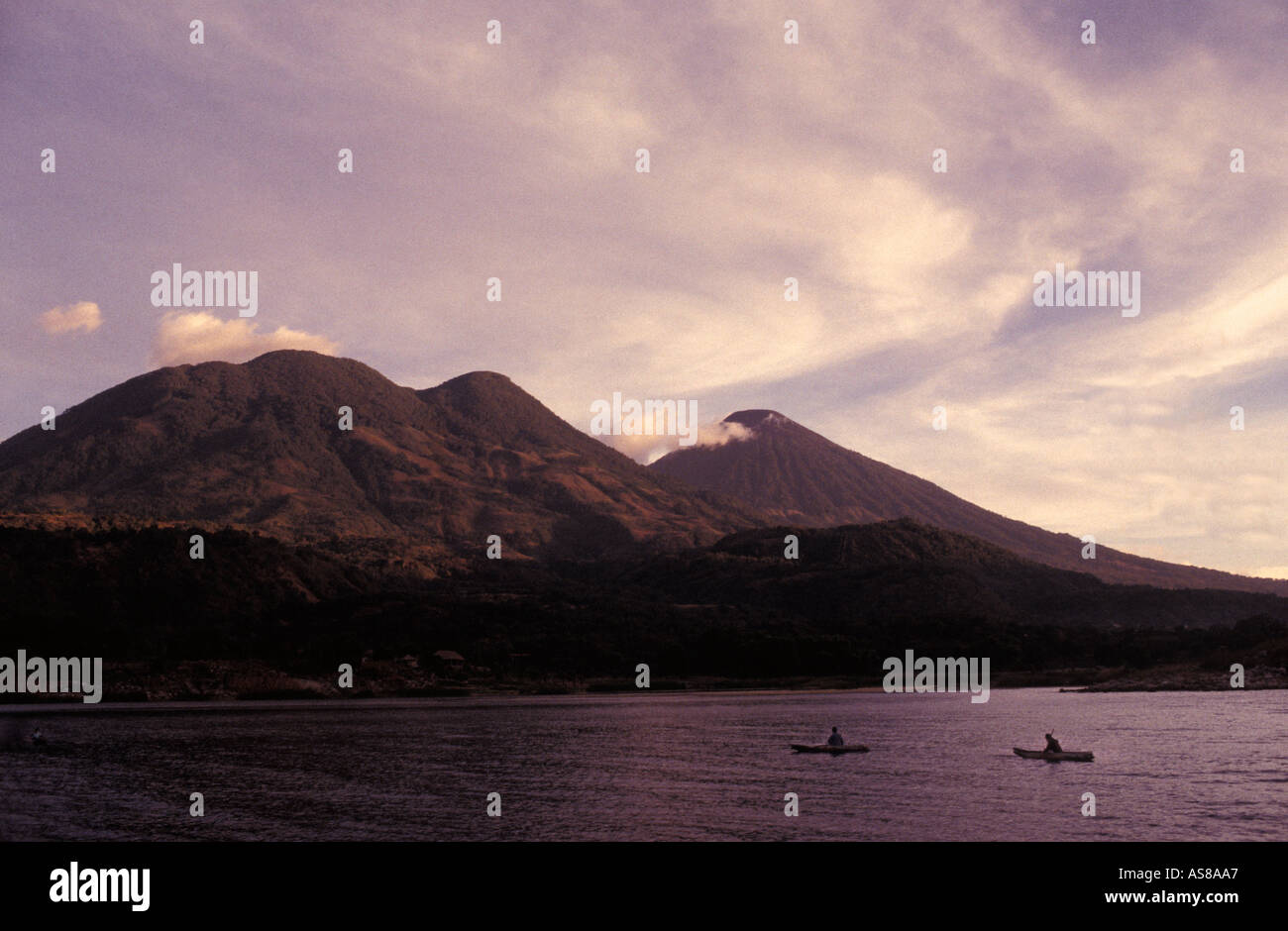 Fishermen in canoes at dawn Santiago Atitlan Lake Atitlan Guatemala Atitlan and Toliman volcanoes - Stock Image
