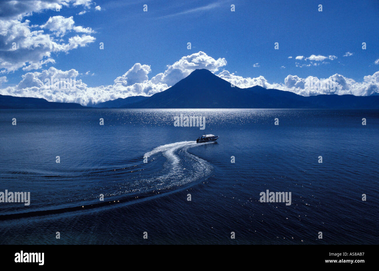 View across Lake Atitlan from the foot of Calle Santander Panajachel Boat speeding across lake San Pedro volcano - Stock Image