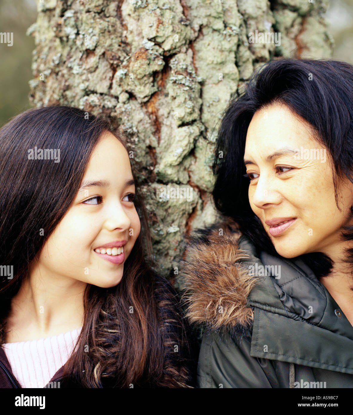 mother and daughter looking towards each other around a tree - Stock Image