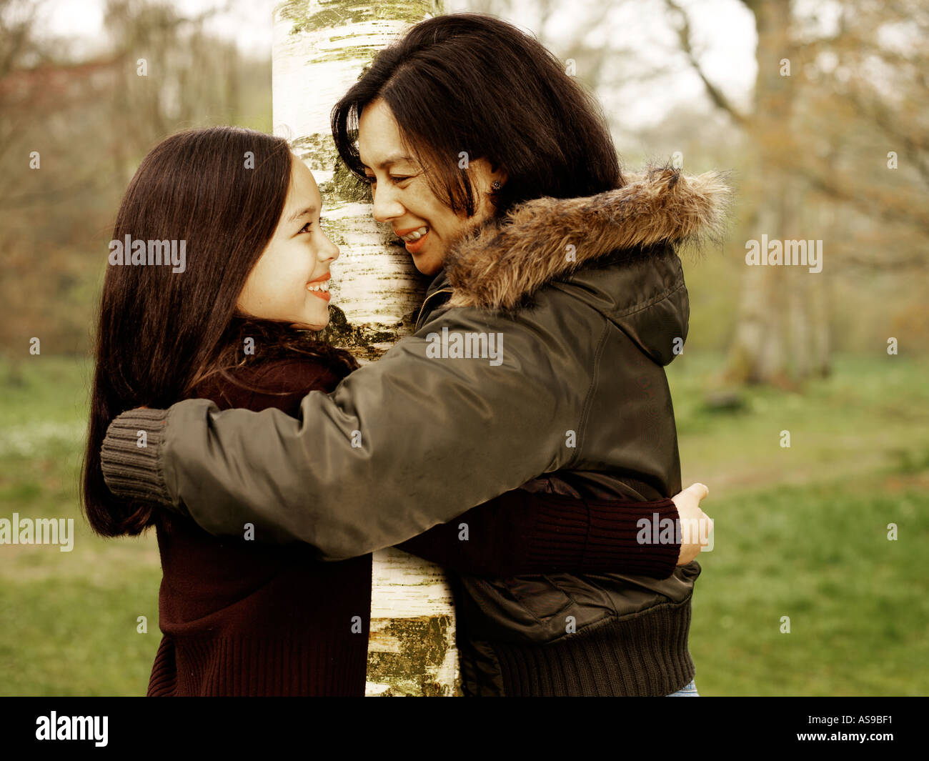 mother and daughter hugging around tree - Stock Image