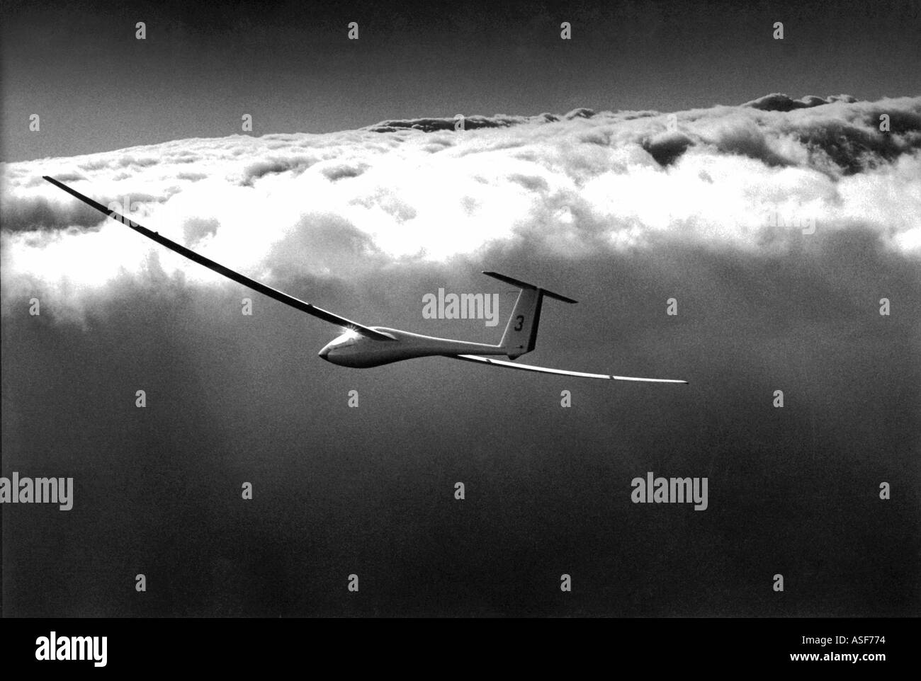 Glider soaring above the clouds - Stock Image
