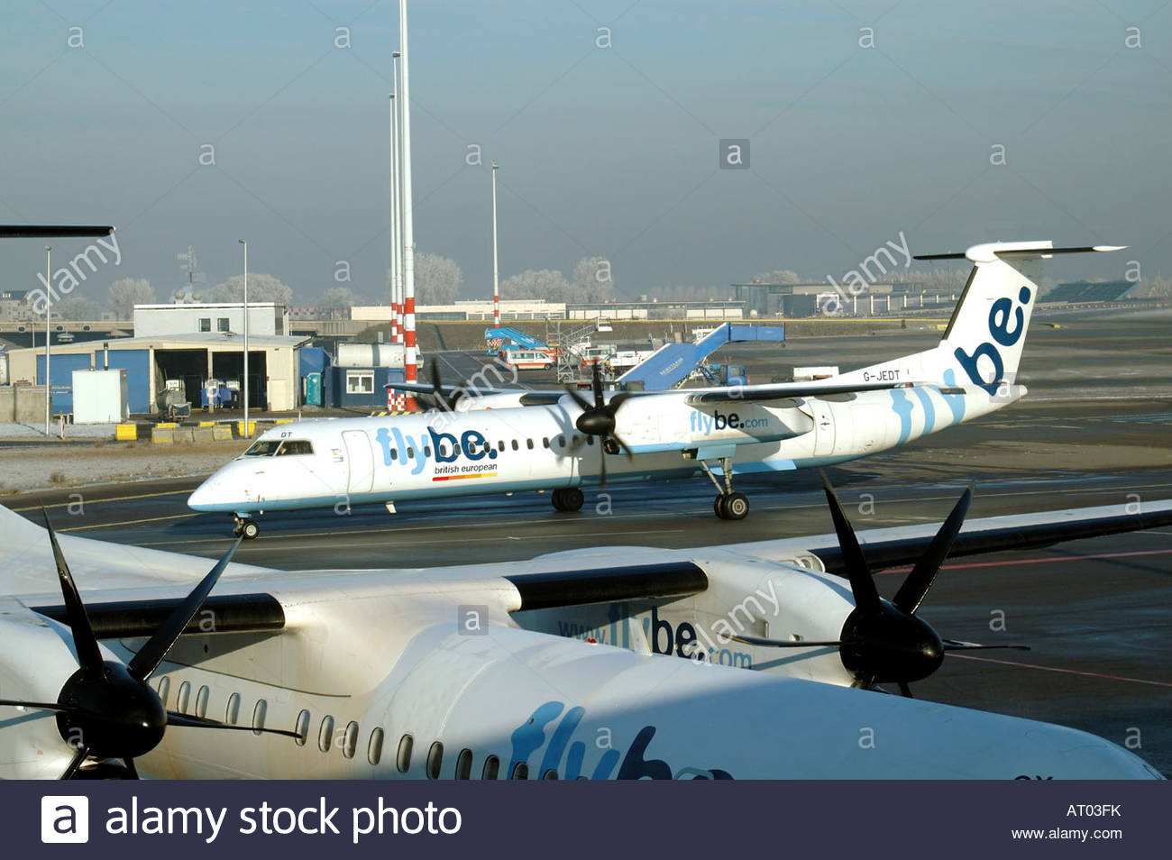 Schiphol The Netherlands Two Flybe Dash 8 pass eachover on the apron. - Stock Image