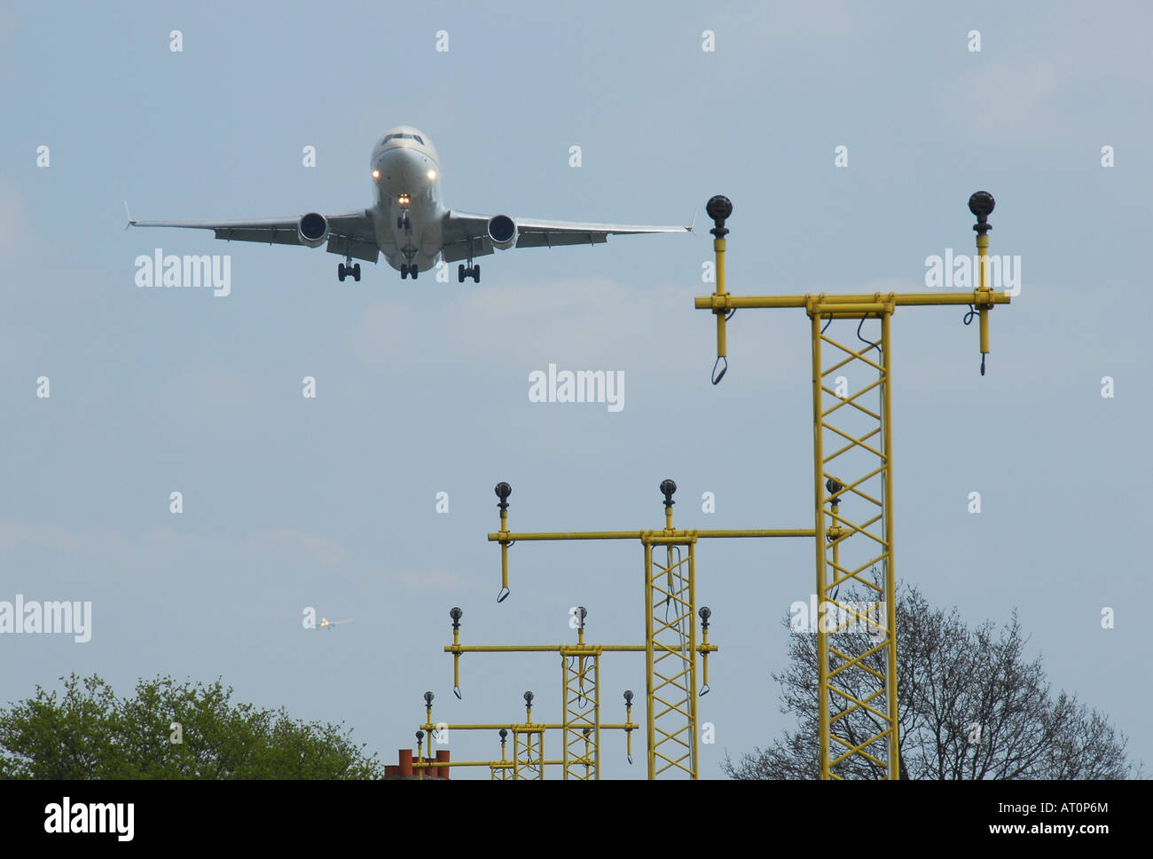 A widebody airliner over the ILS on final approach to Heathrow airport London - Stock Image