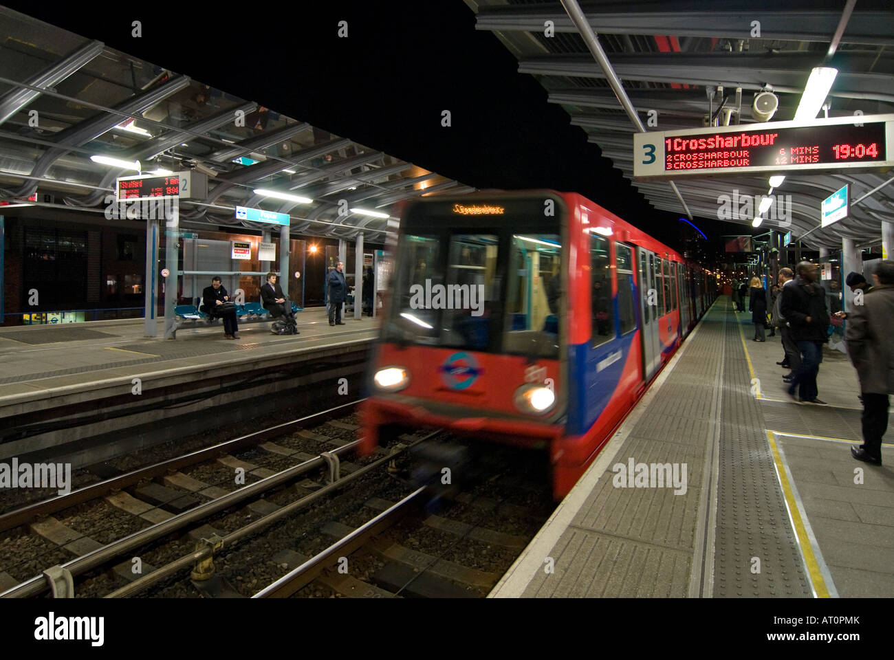 Horizontal wide angle of a Docklands Light Railway train arriving at Poplar station with people waiting on the platform - Stock Image