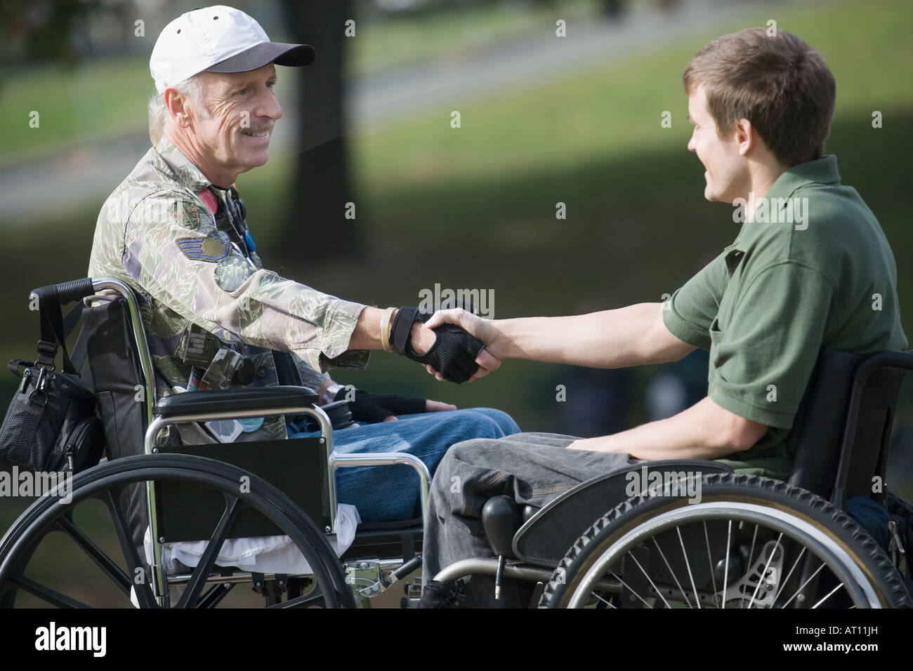 Two war veterans shaking hands with each other - Stock Image