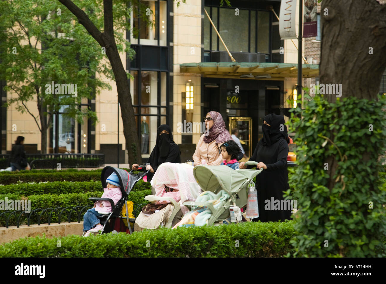 ILLINOIS Chicago Three observant Muslim women pushing strollers in Water Tower Park wearing burqas and head scarf - Stock Image