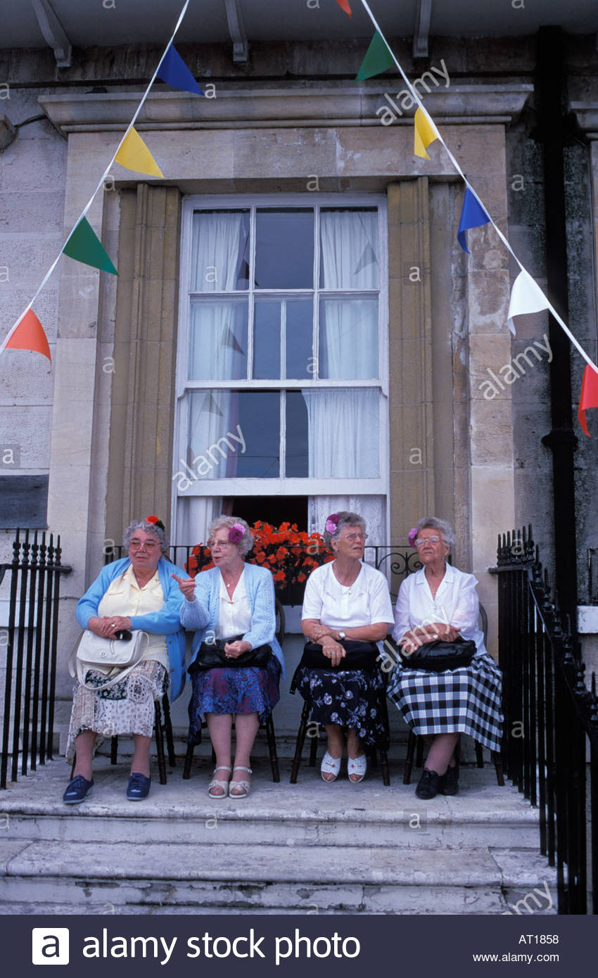 Four elderly ladies watching Weymouth's annual Carnival from their hotel  terrace, UK - Stock Image