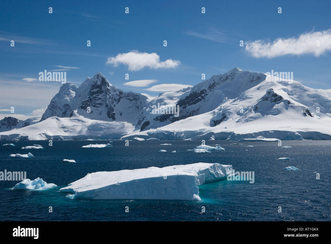 Tabular iceberg floating in front of a snow covered mountain range Stock Photo