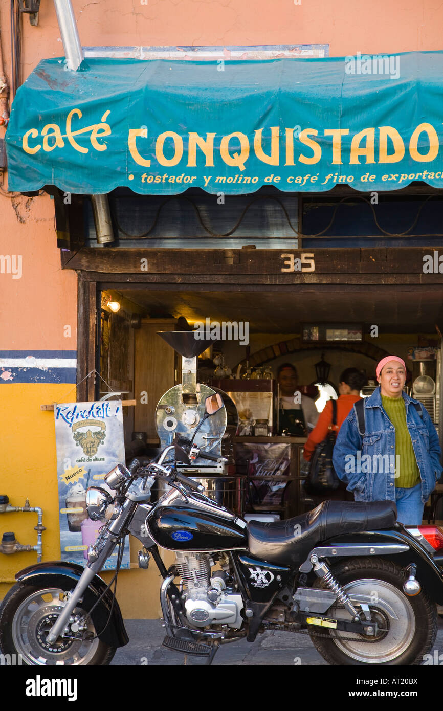 MEXICO Guanajuato Motorcycle and young woman outside coffee cafe awning with store name - Stock Image