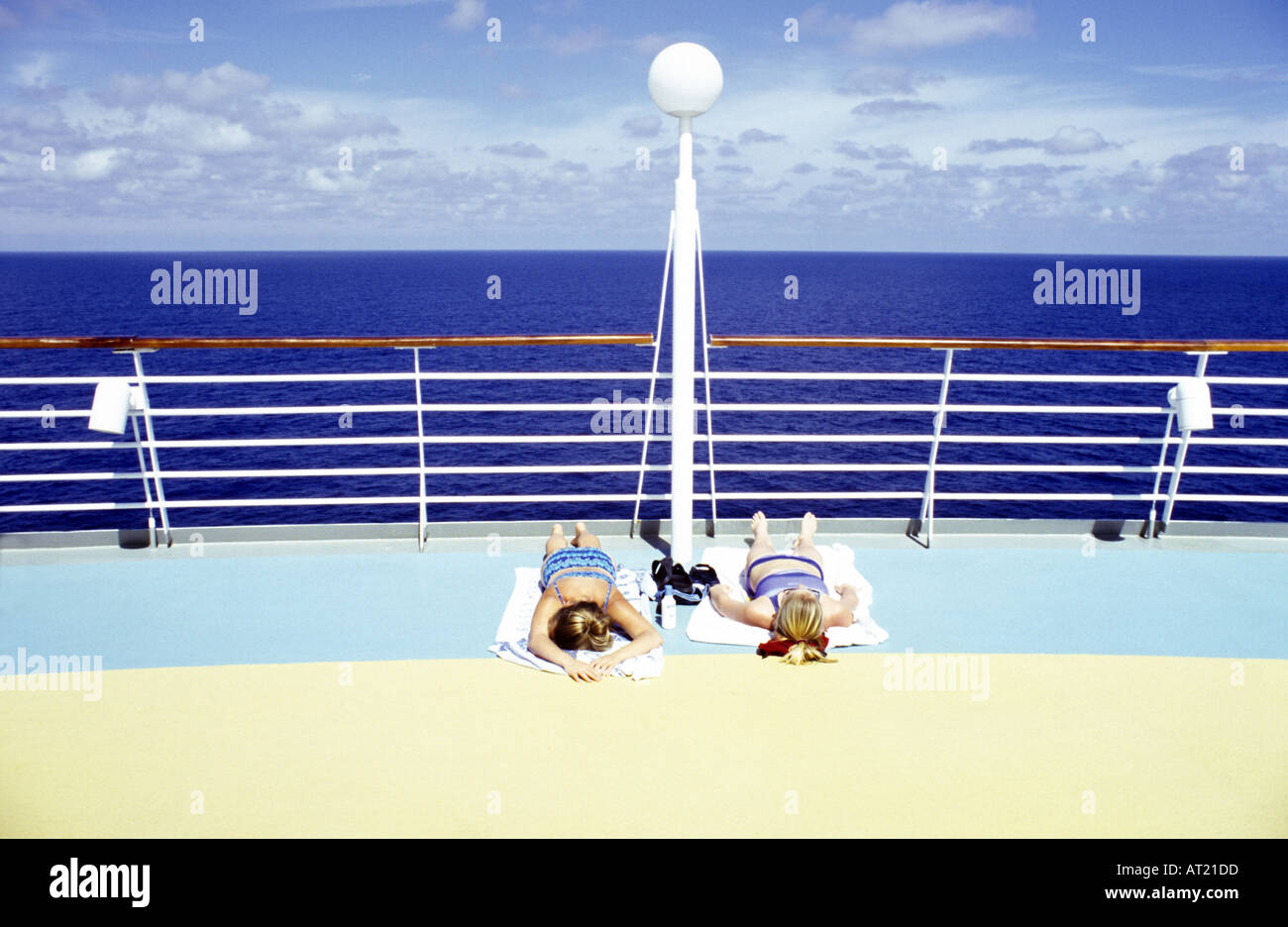 Two women sunbathing on the deck of a cruise ship - Stock Image