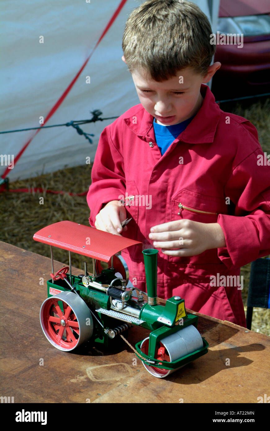 young boy with overalls and toy steam roller - Stock Image