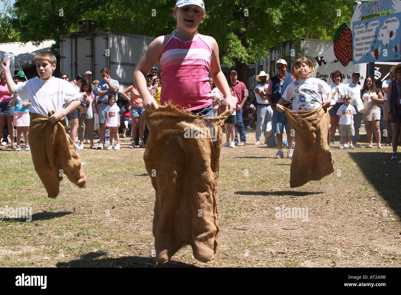 Festival goers participate in a sack race - Stock Image