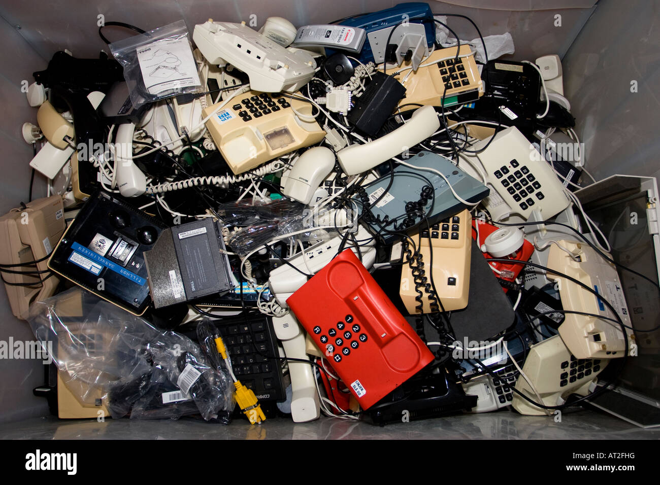 Old telephones for recycling in a container - Stock Image