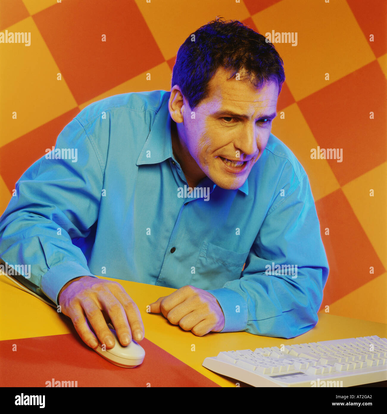A middle aged man looking at a computer screen - Stock Image